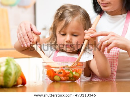 Child girl mixing salad in bowl with mother's help in the kitchen