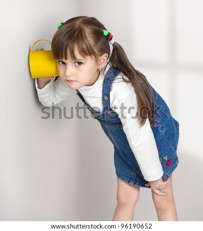 Child girl overhear using cup - stock photo