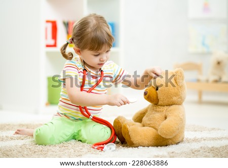 child girl playing doctor and curing plush toy indoors