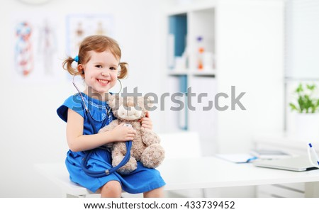 Child girl playing doctor with a teddy bear - stock photo