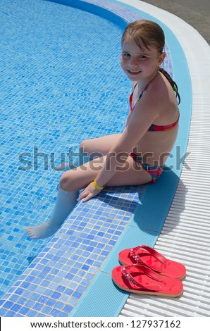 Child girl playing in tropical pool - stock photo