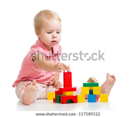 Child girl playing toy blocks and building tower. Isolated on white background