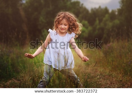child girl playing with leaves in summer forest. Nature exploration with kids. Outdoor rural activities. - stock photo