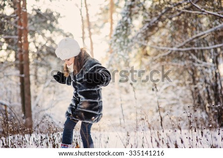 child girl playing with snow on the walk in winter forest. Outdoor activity on winter holidays. - stock photo