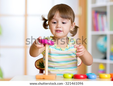 Child girl playing with toy indoors at home - stock photo