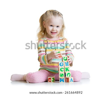 child girl playing with wooden toys on floor isolated - stock photo