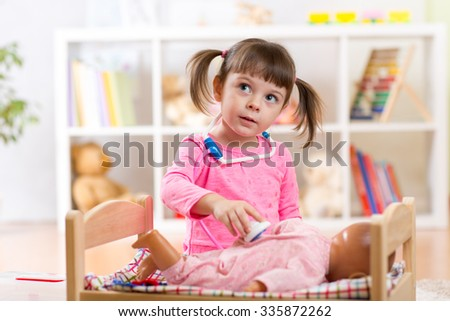 Child girl plays doctor examining baby doll patient with toy stethoscope - stock photo