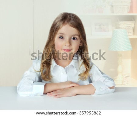 Child girl portrait indoor cozy home.Kid female in room study.Pupil at desk on light background.Elementary school concept.Knowledge wallpaper. - stock photo