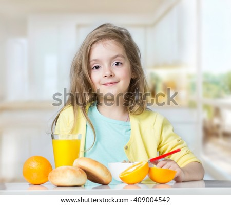 Child girl sitting at table indoors eating fruits buns cereal.Healthy lifestyle kid's vitamin nutrition concept.beautiful caucasian toddler with glass of orange juice and bowl. - stock photo