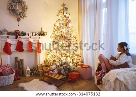 Child girl sitting near decorated Christmas tree and fireplace in comfortable chair at home - stock photo