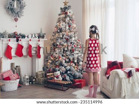 Child girl standing near decorated Christmas tree and fireplace in beautiful hotel room in the holiday morning - stock photo