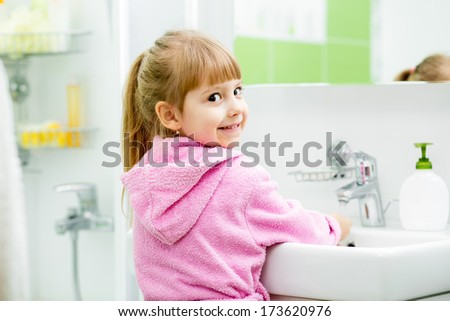 child girl washing her face and hands in bathroom - stock photo