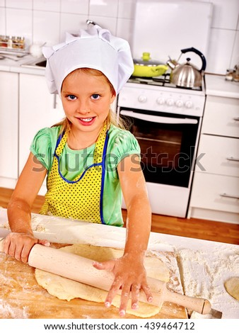 Child girl wearing cooking hat cooking knead dough at kitchen. - stock photo