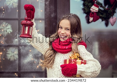 Child girl welcome guests and holding presents, snow weather, house door is decorated before Christmas - stock photo