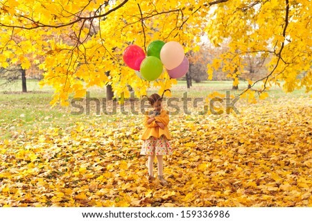 Child girl with colorful balloons on her hear walking alone in autumn forest - stock photo