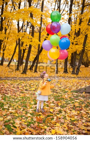 Child girl with colorful balloons walking alone in autumn forest - stock photo