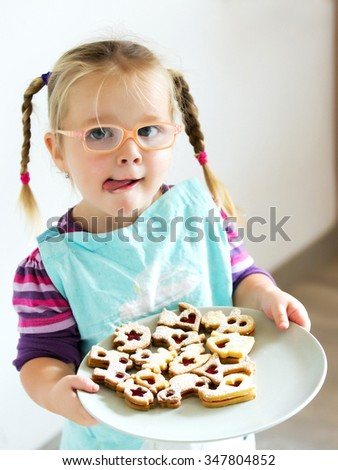 child girl with glasses have protruding tongue and hold plate with xmas cookies - stock photo