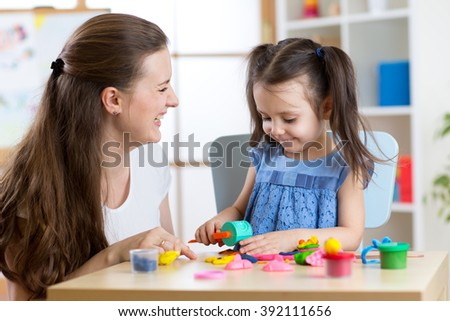 Child girl with her mother sculpts from clay