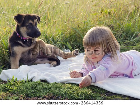 Child girl with puppy dog relaxing on blanket in grass at nature meadow. - stock photo