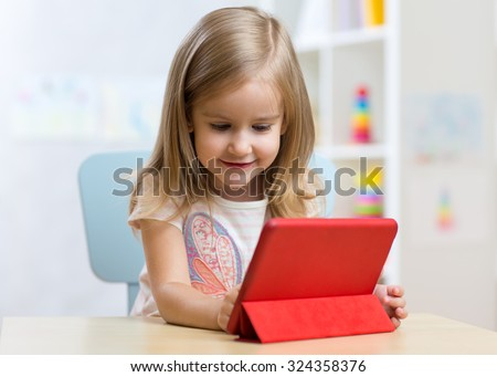 Child girl with tablet computer at table at home. - stock photo