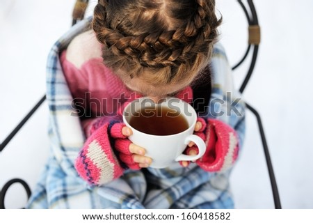 Child girl wrapped in warm blanket drinking hot tea outdoors - stock photo