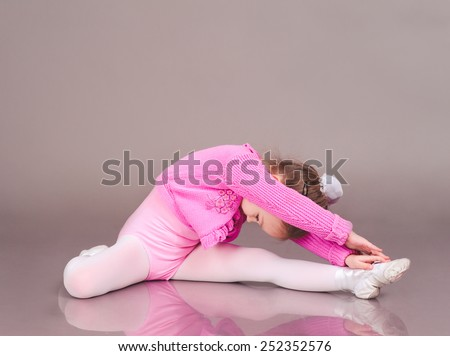 Child girl 3-4 year old doing fitness exercises over gray - stock photo