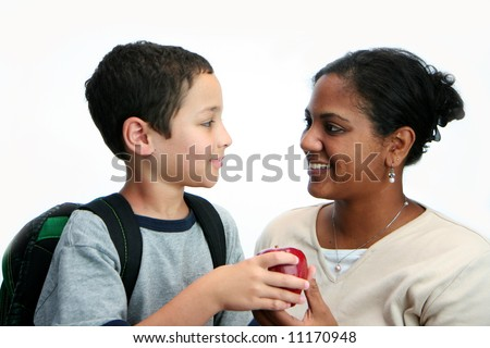 Child giving apple to his teacher - stock photo