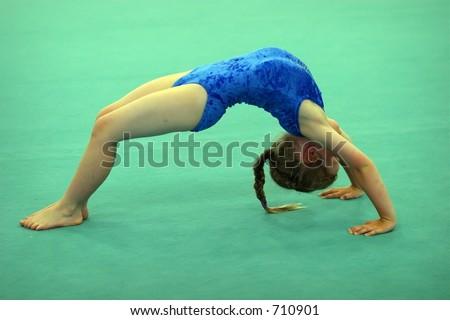 child gymnast wearing a blue leotard on the floor in a bridge shape - stock photo