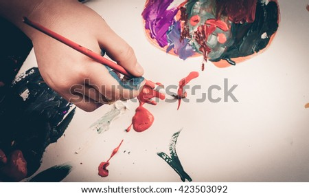Child hand coloring on paper with acrylic - stock photo