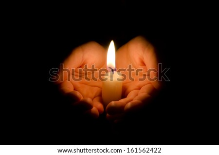 Child hand holding a burning candle in dark - stock photo