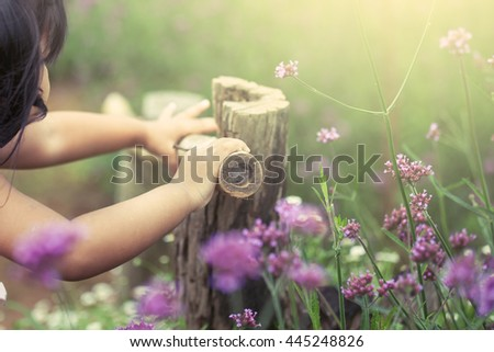 Child hand holding bamboo railing in the flower garden in vintage color tone