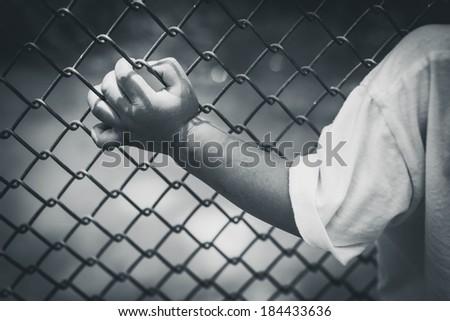 child hand in jail , hand clutching prison,no escape,monochrome - stock photo