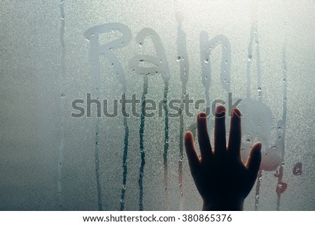 Child hand on abstract drops foggy glass background. Rain written on fogged window, close up sign.  - stock photo