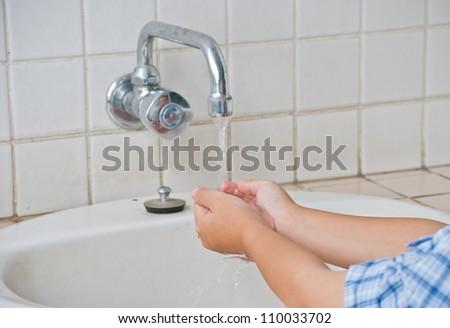 Child hand washing in the washbasin - stock photo