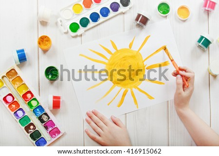 Child hand with brushes drawing on white paper yellow sun. Child drawing top view. - stock photo