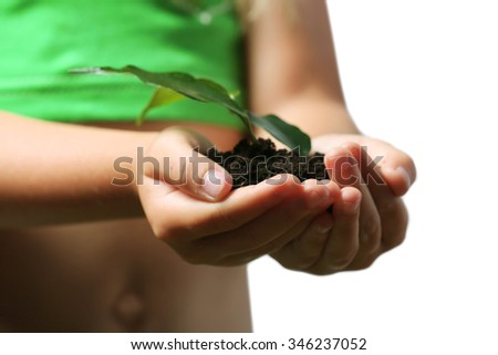 Child handful with soil and small green plant close up - stock photo