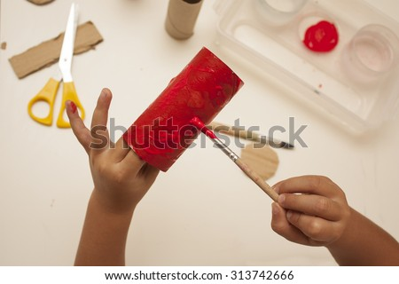 child hands with painting and cutting with scissors to make craft - stock photo