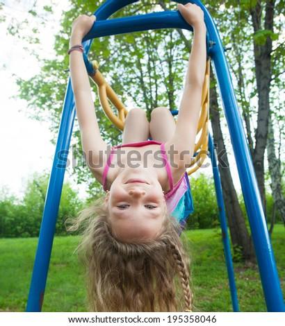 Child hanging on horizontal bar - stock photo