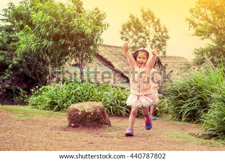 Child happy little girl  running and having fun in the garden in vintage color tone - stock photo