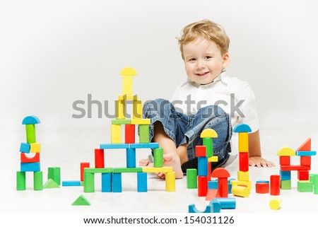 Child happy playing toy blocks over white background - stock photo