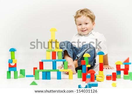 Child happy playing toy blocks over white background - stock photo