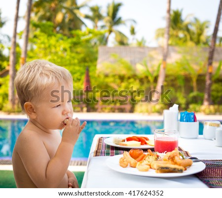 Child has a breakfast near a swimming pool - stock photo