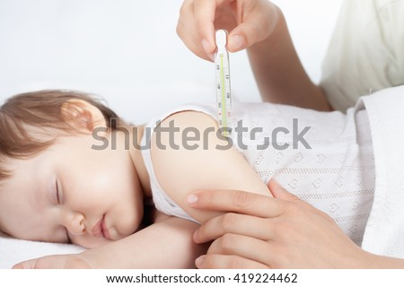 Child has a high temperature or fever. Doctor or mother measures the temperature of baby using a thermometer. Closeup. Flu.