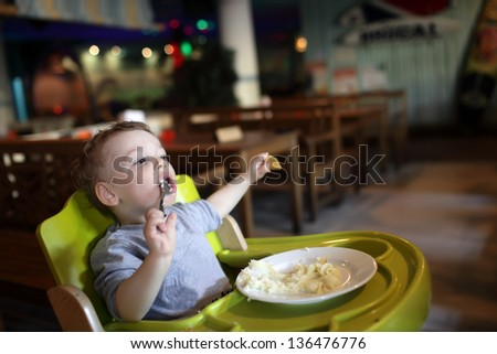 Child has a lunch in a high chair at a restaurant - stock photo