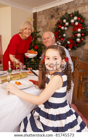 Child having Christmas dinner with grandparents - stock photo