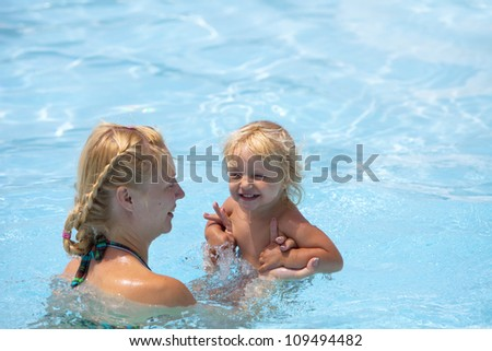 Child having fun in water with mom.