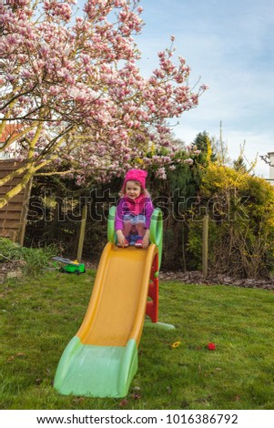 child having fun on a childrens slide in the backyard