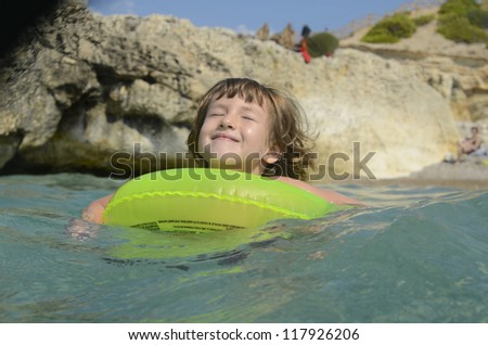 Child  having fun with inflatable ring in the sea on summer vacation
