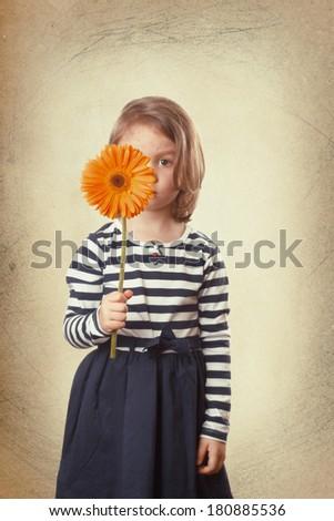Child hiding his face behind a orange gerbera flower - stock photo