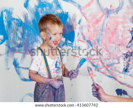 Child himself dirty in the paint and looks into the camera. Child has fun and stain the wall. Children's creativity. Art for baby. - stock photo